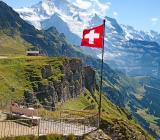 Schweiziska flaggan i alpmiljö. Foto: Colourbox